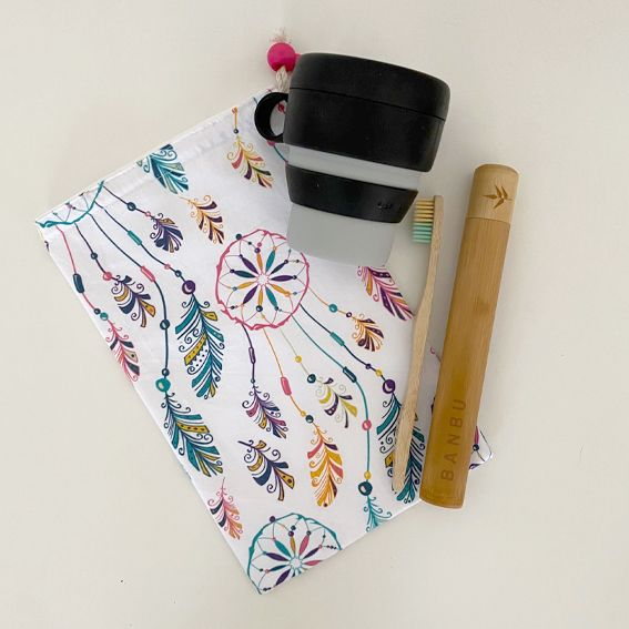 Bodegón con bolsa para bocadillo, taza reutilizable, funda para cepillo de dientes y cepillo de dientes de bambú