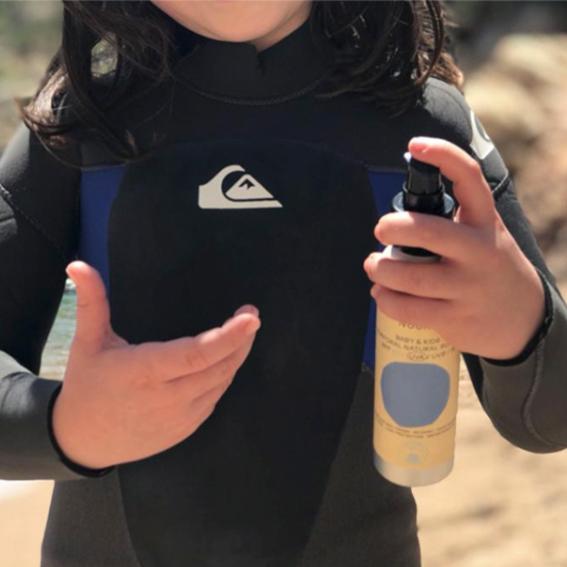 niña con envase de protector solar pediátrico NUURA