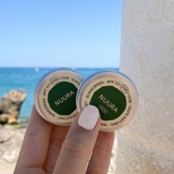 Mano sujetando latas de protector solar de Nuura Care