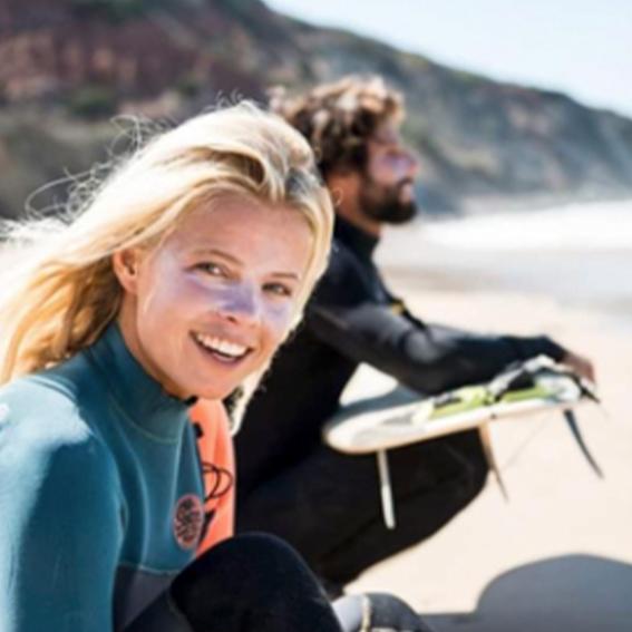 Surferos en la playa. La mujer lleva aplicada en la cara crema protectora