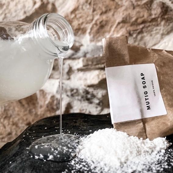 Botella echando jabón Mutig Soap sobre sus propios ingredientes