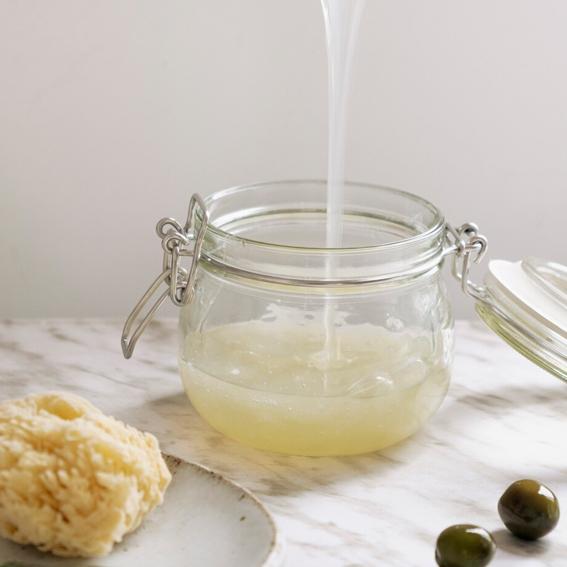 Tarro de cristal que está siendo rellenado de jabón Mutig Soap