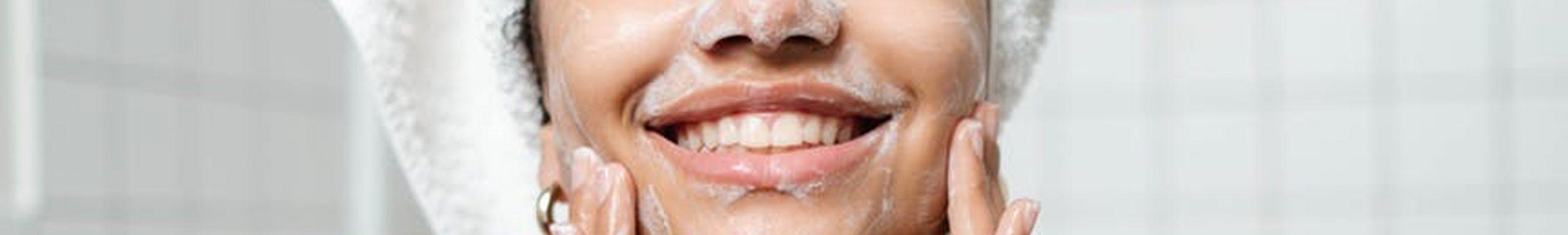 rostro de mujer sonriente, lavándose la cara